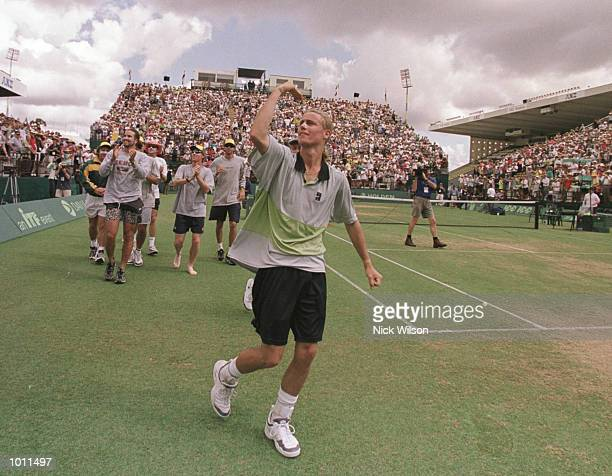 Lleyton Hewitt of Australia leads the Australia team around on a lap of honour after his 64 75 62 victory over Yevgeny Kafelnikov of Russia during...