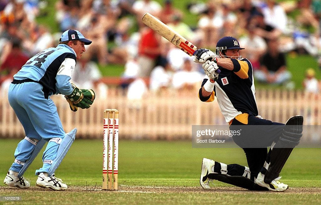Matthew Elliott of the Victorian Bushrangers hits out through mid wicket during his century as wicketkeeper Brad Haddin of the NSW Blues looks on during the Mercantile Cup Cricket at the North Sydney Oval, Sydney, Australia. Mandatory Credit: Scott Barbour/ALLSPORT