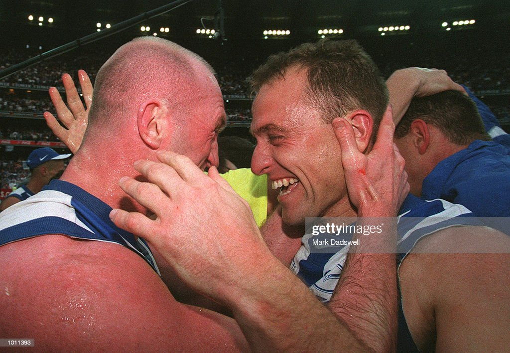 Michael Martyn #4 and John Longmire #35 for the Kangaroos celebrate on the ground after their win, in the AFL Grand Final match between the Kangaroos and Carlton, played at the Melbourne Cricket Ground, Melbourne, Australia. The Kangaroos defeated Carlton. Mandatory Credit: Mark Dadswell/ALLSPORT