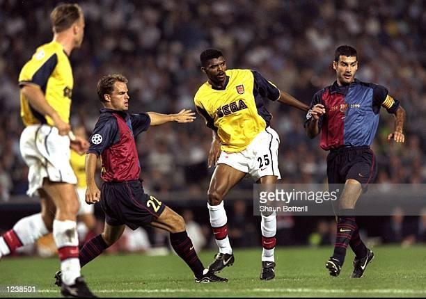 Nwankwo Kanu of Arsenal is closed down by Frank de Boer and Josep Guardiola of Barcelona during the Barcelona v Arsenal UEFA Champions League Group B...