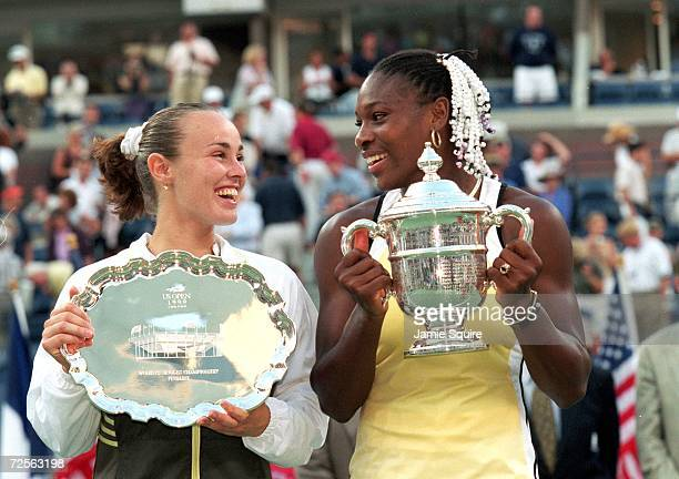 Serena Williams of the USA and Martina Hingis of Switzerland smile and pose with their trophies after their match in the US Open at the USTA National...