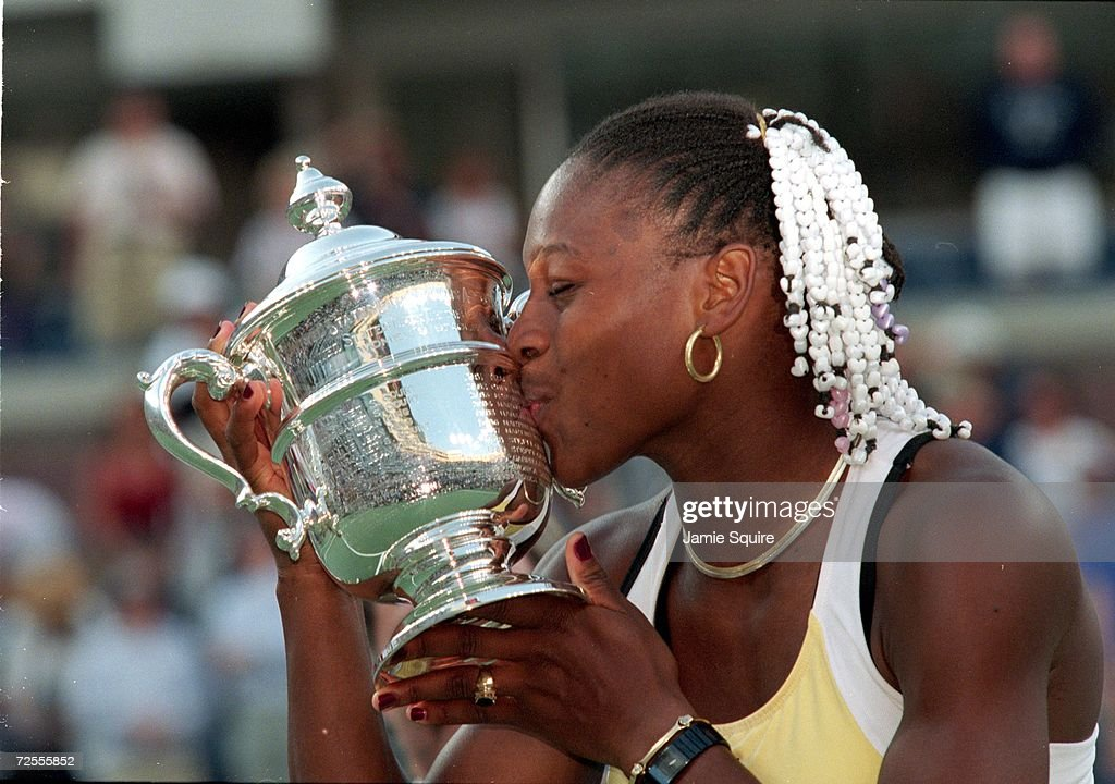 Serena Williams of the USA kisses her trophy after winning a match against Martina Hingis of Switzerland during the US Open at the USTA National...