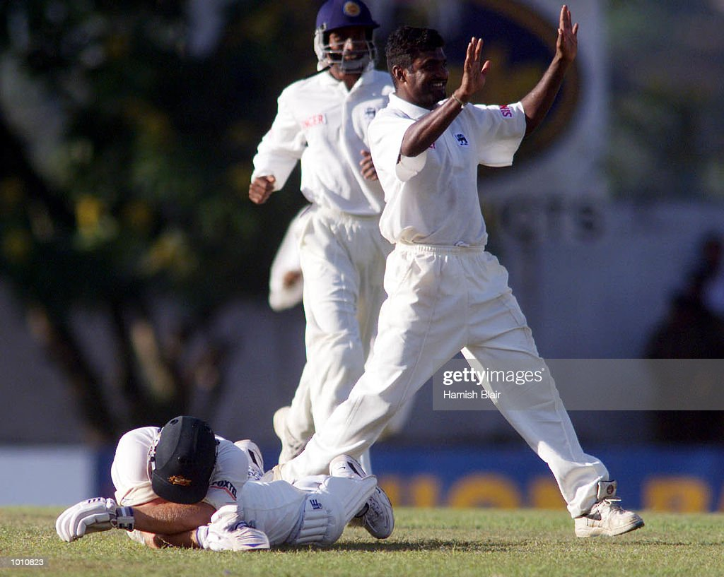 Shane Warne of Australia lies devastated on the ground as Muttiah Muralitharan of Sri Lanka celebrates his run out, during day two of the First Test between Sri Lanka and Australia at Asgiriya Stadium, Kandy, Sri Lanka. Mandatory Credit: Hamish Blair/ALLSPORT
