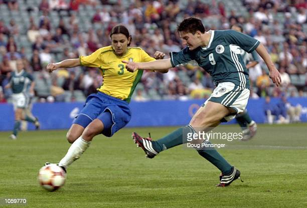 Birgit Prinz of Germany scores the second goal despite the tackle of Juliana of Brazil as Germany defeat Brazil 20 in the womens Bronze medal soccer...