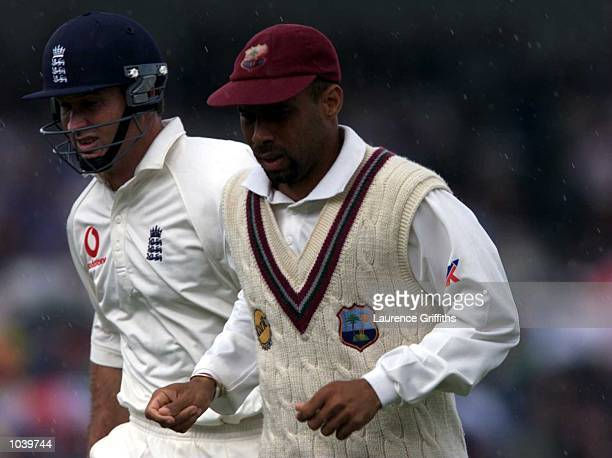 Captain Jimmy Adams of the West Indies and batsman Graeme Hick of England leave the pitch as the showers come down during the Fifth Cornhill...