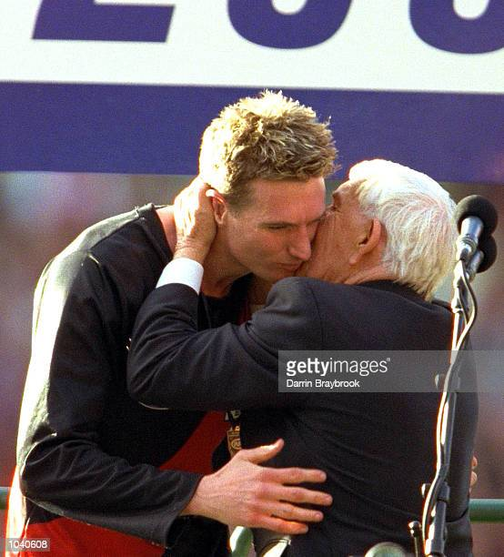 James Hird for Essendon is hugged by Lou Richards on the podium after being awarded the Norm Smith medal after Essendons win in the AFL Grand Final...
