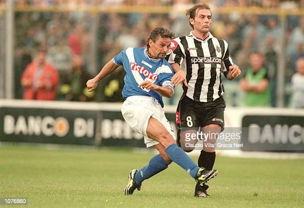 Roberto Baggio of Brescia shoots past Antonio Conte of Juventus during the Coppa Italia match played at the Estadio Rigamonti in Brescia Italy The...