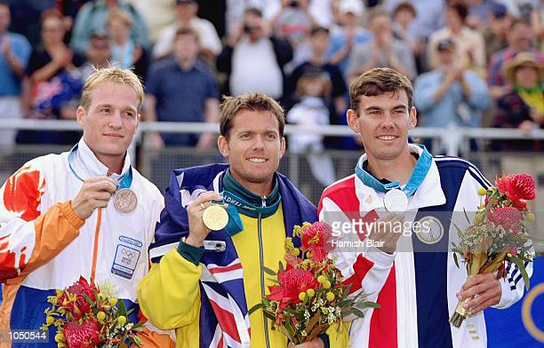 Simon Fairweather of Australia on the podium after winning a gold medal in the Mens Individual Archery alongside silver medallist Victor Wunderle of...
