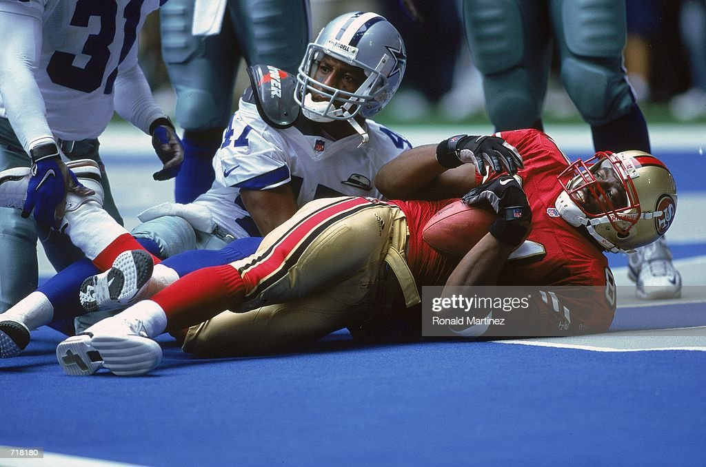 Terrell Owens the San Francisco 49ers lands in the endzone for a touchdown with Ryan McNeil of the Dallas Cowboys during the game at the Texas...