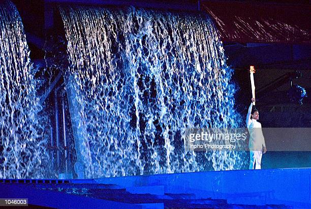 Torch bearer Cathy Freeman holds the Olympic Flame aloft during the Opening Ceremony of the Sydney 2000 Olympic Games at the Olympic Stadium in...