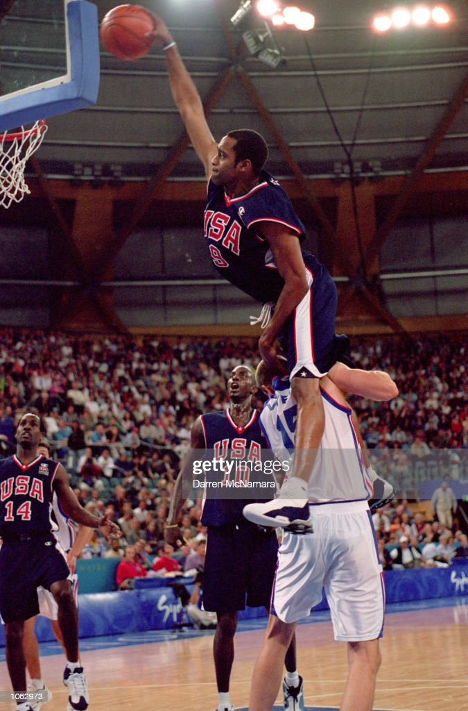 Vince Carter of the USA leaps over Frederic Weis of France to dunk during the Mens Basketball Preliminaries at the Dome in the Olympic Park on Day 10...