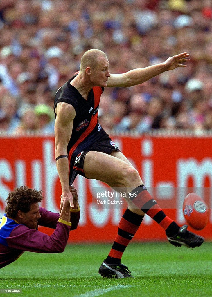 Darryl White for Brisbane tackles Sean Wellman for Essendon as he kicks the ball during the 2001 AFL Grand Final match between the Essendon Bombers...