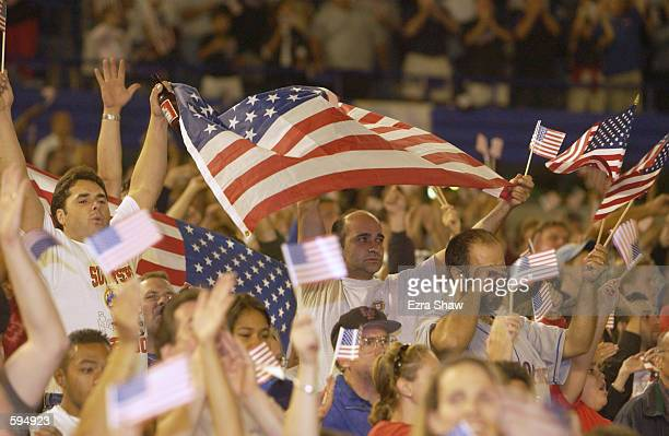 Fans wave American flags while Marc Anthony signs the National Anthem before the Mets game against the Atlanta Braves at Shea Stadium in Flushing New...