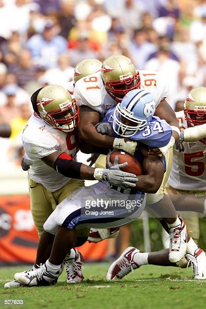 Jeff Womble and Kendyll Pope of Florida State tackles Andre'' Williams of North Carolina Tar Heels during the game at Kenan Stadium in Chapel Hill...