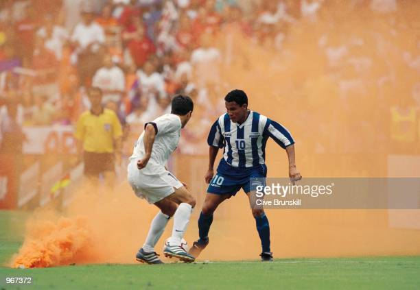 Julio Cesar De Leon of Honduras and Preki Radosavljevic of USA play around a flare thrown onto the pitch during the FIFA 2002 World Cup Qualifier...