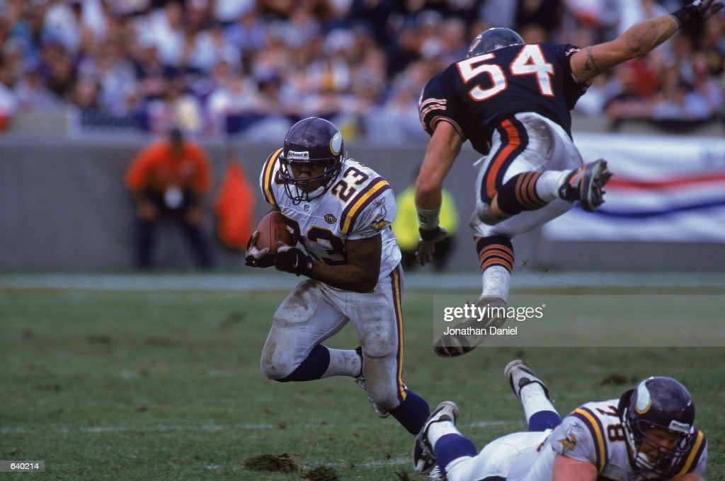 Michael Bennet of the Minnesota Vikings runs with the ball as teammate Matt Birk tries to block Brain Urlacher of the Chicago Bears during the game...