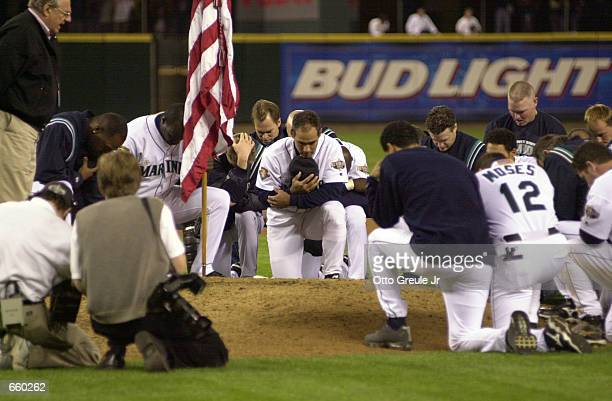 Players of the Seattle Mariners pay their respect to the flag as they are celebrating their title win of the American League Western Division after...
