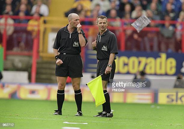 Referee Mike Dean discusses the situation with his assistant as a magazine is thrown onto the pitch during the FA Barclaycard Premiership match...