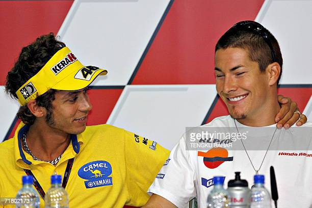 Italian rider Valentino Rossi of Yamaha places his arm over the shoulder of US rider Nicky Hayden of Honda during a preevent press conference at the...