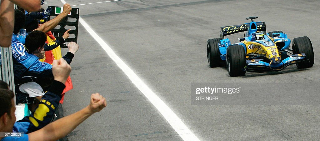 Renault Formula One driver Giancarlo Fisichella of Italy waves to his team members after crossing the finishing line of the Malaysian F1 Grand Prix at Sepang International Circuit, 19 March 2006. Renault's Giancarlo Fisichella of Italy won the Malaysia round while his teammate Fernando Alonso of Spain finished second. AFP Photo/Andy WONG