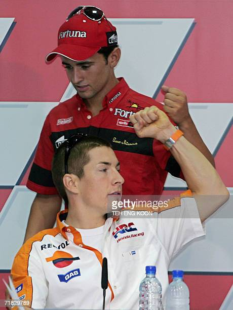Spain's 250cc motocycle rider Hector Barbera walks by US motocycle rider Nicky Hayden during a press conference at the International Racing Circuit...