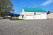 Separate garage building with three garage doors and gravel driveway around