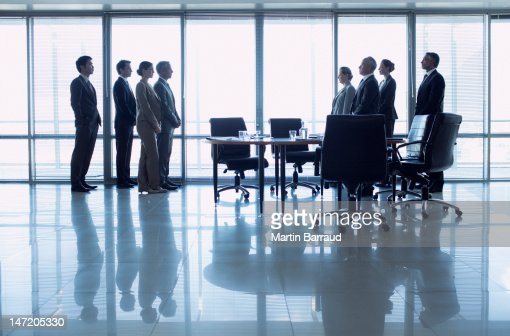 Separate groups of business people facing off in conference room : Foto de stock