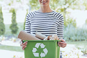 Aware woman separated paper from other waste to green container to save natural resources