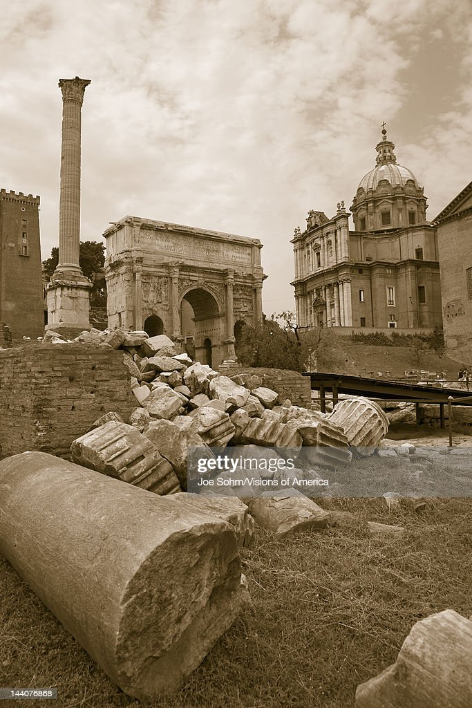 Sepia image of Roman ruins with Column of Foca with Roman Forum in background in Rome Italy Europe