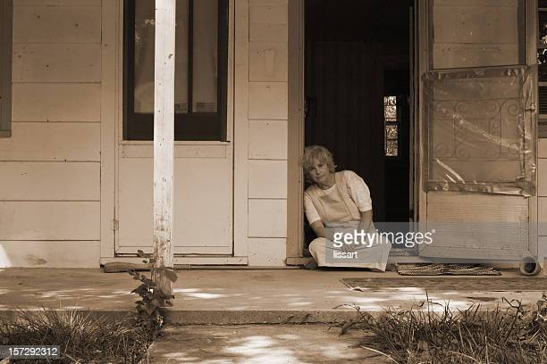 Sepia picture of elderly woman sitting at the doorstep