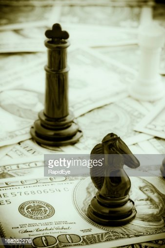 Sepia-toned view of  chessmen resting on many US dollars