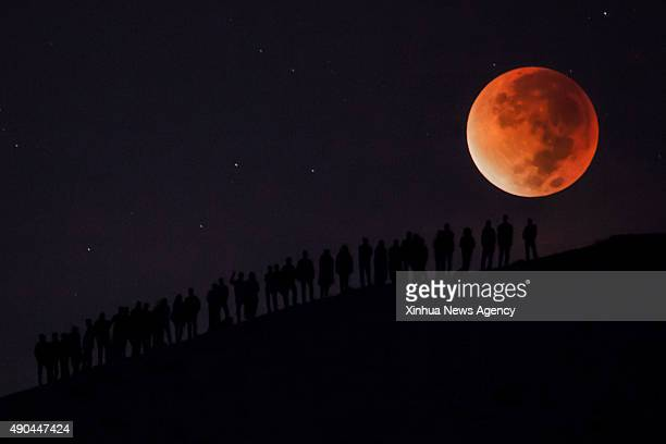 BETHLEHEM Sept 28 2015 Palestinians enjoy the view of a socalled supermoon during a total lunar eclipse in the West Bank city of Bethlehem early on...