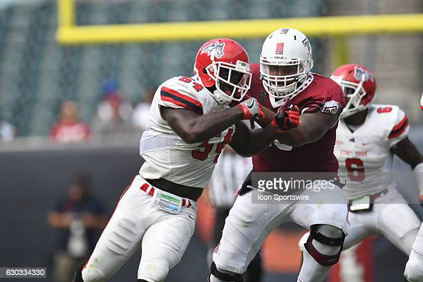 Stony Brook Seawolves linebacker Humphrey Anuh and Temple Owls offensive lineman Dion Dawkins battle during a NCAA Football game between Stony Brook...