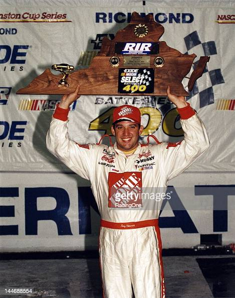 Tony Stewart holds his trophy over his head after winning the first NASCAR Cup race of his career the Exide NASCAR Select Batteries 400 at Richmond...