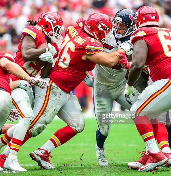 Kansas City Chiefs running back Jamaal Charles follows a lead block by Kansas City Chiefs offensive lineman Laurent DuvernayTardif as Houston Texans...
