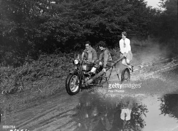 A motorcyclist riding through a puddle has a pole attached to his machine in the place of a sidecar and on it are balanced two young women