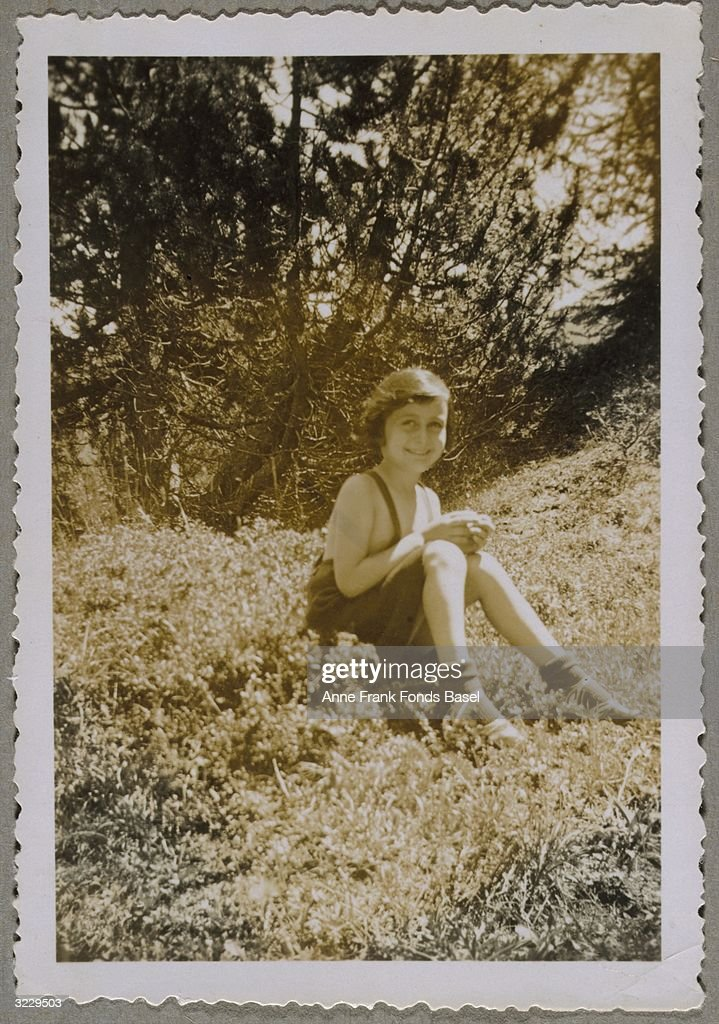 A portrait of Anne Frank (1929 - 1945) sitting on tall grass in front of a tree near Villa Laret (owned by Olga Spitzer), Sils-Maria, Switzerland. From Anne Frank's photo album.