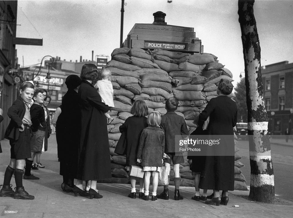 A group of people gather around a police public call box in London, which has been surrounded by sandbags for protection during World War II.