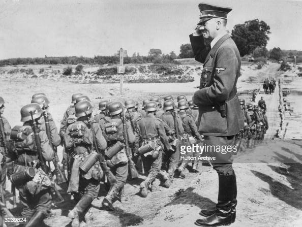 German Fuhrer Adolf Hitler salutes as he oversees his military troop during the Nazi occupation of Poland The troops march in formation toward a...