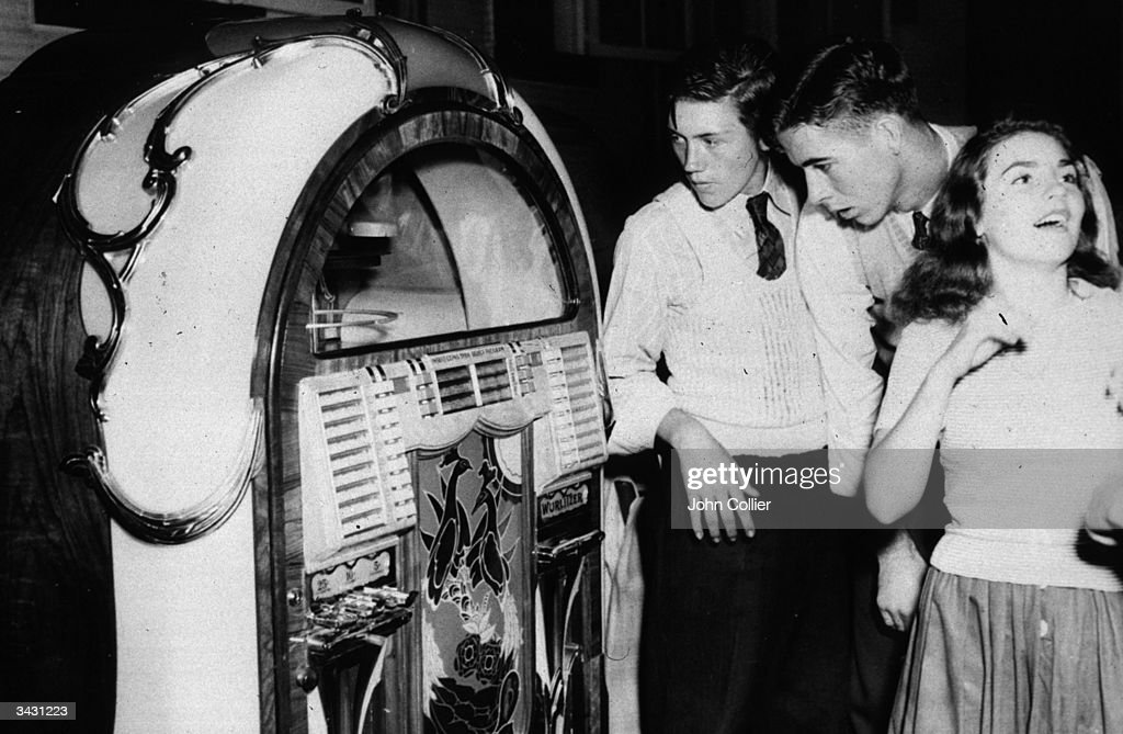 A group of teenagers standing by a jukebox in a dance hall in Richwood, West Virginia.
