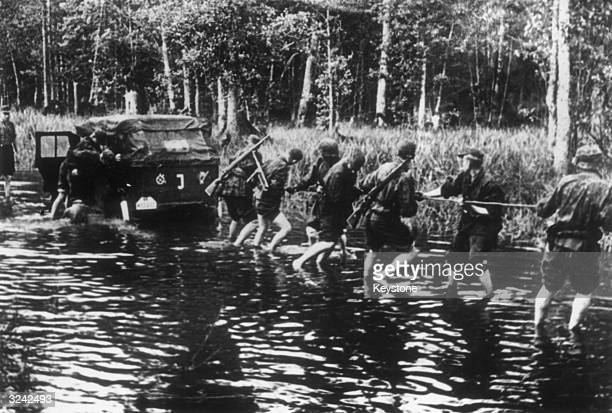 Members of the Wehrmacht try to budge a German staff car which has become stuck on a flooded road on the Dnieper Front between Russia and Poland