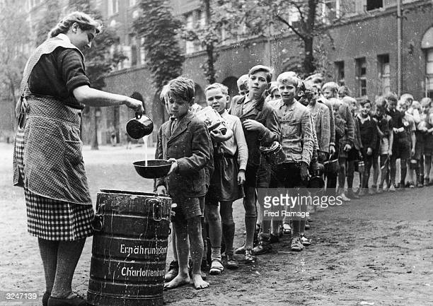 Boys in postwar Berlin are served a ration of gruel in the playground of their school in the Charlottenburg district The rations are provided by the...
