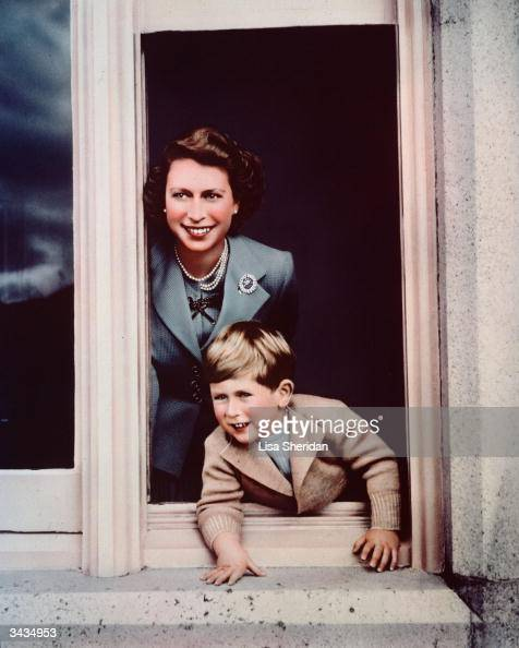 Prince Charles and his mother Princess Elizabeth looking out of a window at Balmoral