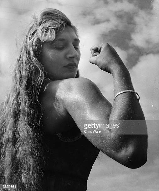 Twentyone year old Alice Penfold a professional strong woman from Bury near Pulborough Sussex flexes her biceps She can tear telephone directories in...