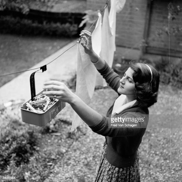 A British housewife hangs out her washing and with the help of a peg carrier which runs along the line she never has to bend down to pick up handfuls...