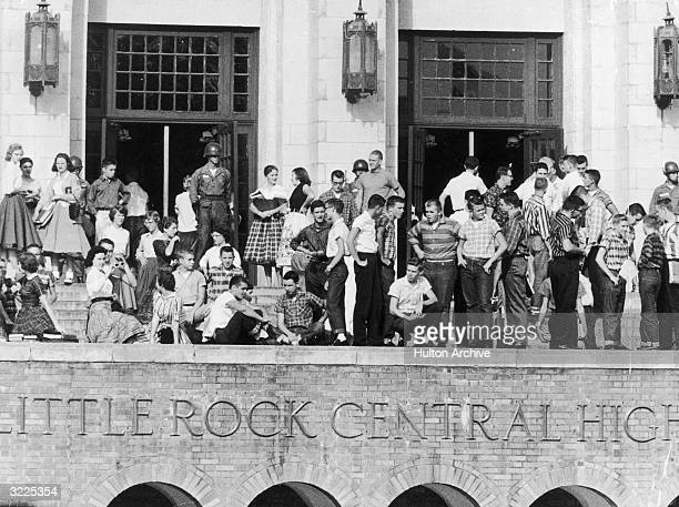 A view of National Guardsmen standing outside Little Rock Central High School and a large group of white students standing with them to prevent any...