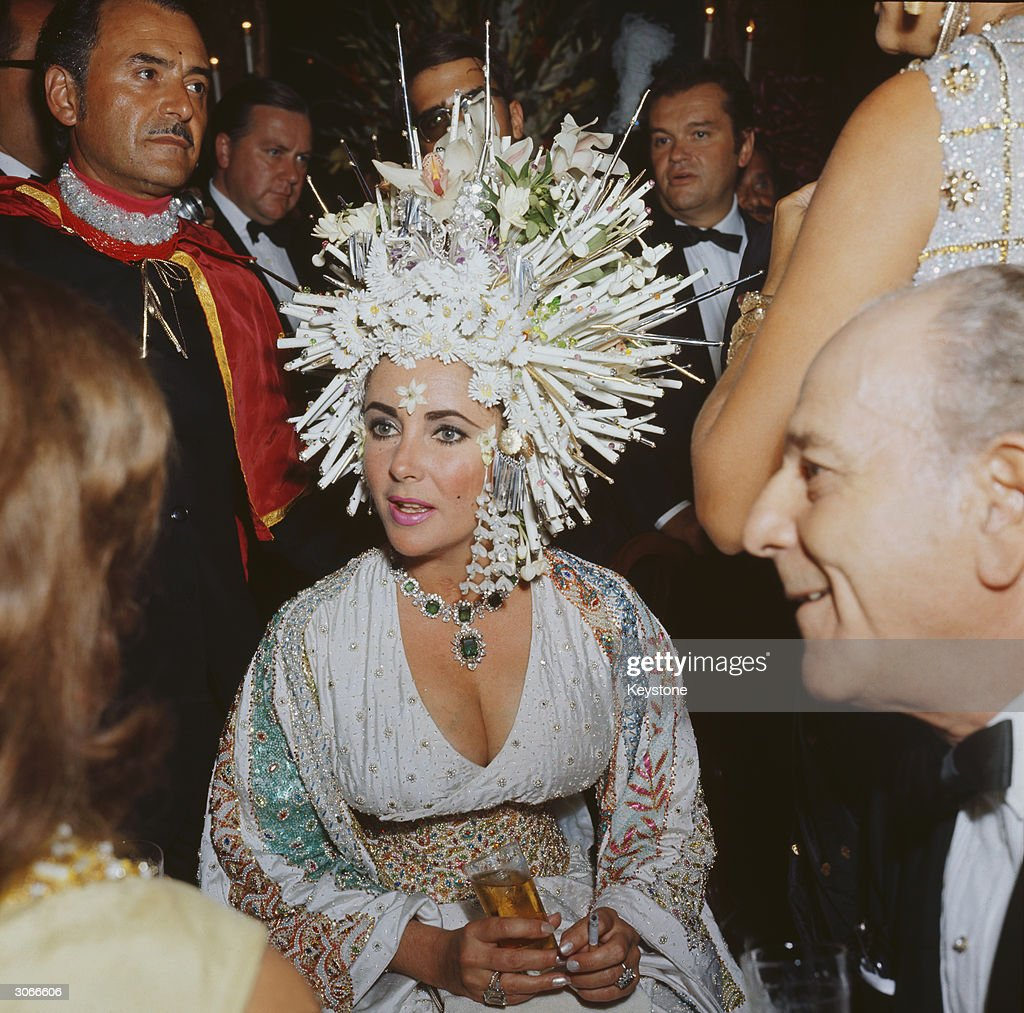 English movie star Elizabeth Taylor attends a social function wearing an elaborate headdress of pearls and fake flowers, a jewelled dress and an emerald necklace.