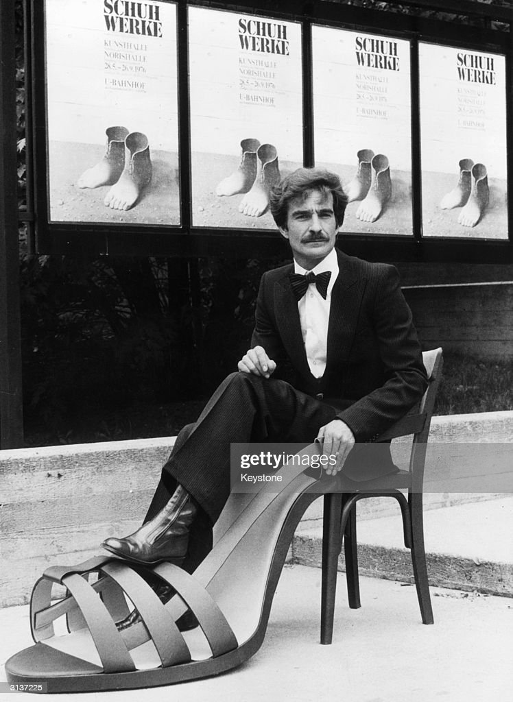 Rainer Reisky on tour with the collection of the German Shoe Institute visits a shoe exhibition commemorating the 400th anniversary of the death of Nuremberg shoemaker Hans Sachs. He sits in the 'shoe-seat' by Austrian feminist artist Birgit Jurgenssen.