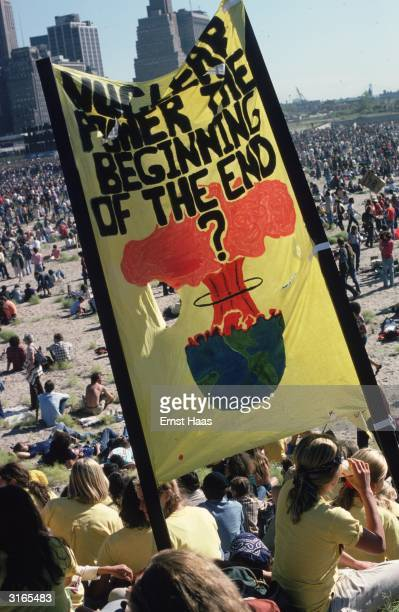 Antinuclear demonstrators gather in a large open space in New York A banner they are carrying reads 'Nuclear Power The Beginning Of The End'