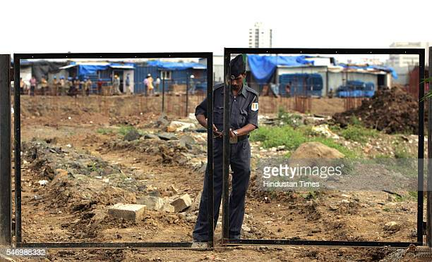 Private Security Guard Sense of Security A security guard locks a nonexistent gate to protect the land at Bandra Kurla complex